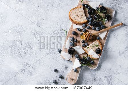 Berries blackberry and blueberry, honey on dipper, rosemary, sliced goat cheese with bread served on wooden board over gray texture background. Summer sandwich. Top view with space