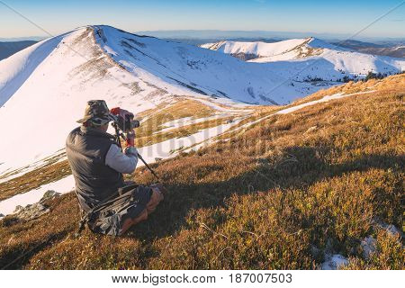 Photographer with a camera taking photos of beautiful winter mountain valley in a morning light. Carpathians Ukraine Europe.