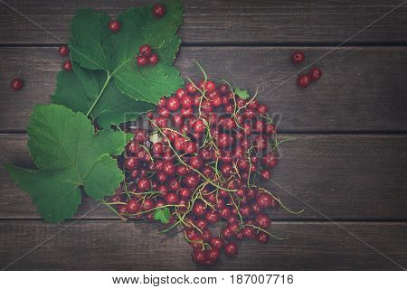 Fresh ripe red currants heap on rustic wood background. Natural organic berries with green leaves scattered on weathered grey wooden table. Vintage dark filter