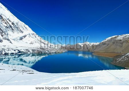 Tilicho Lake in Annapurna Conservation Area Nepal. Mountains reflecting in the water of the lake.