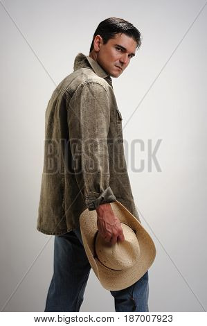 The darling cowboy waits with a cowboy hat in hand.