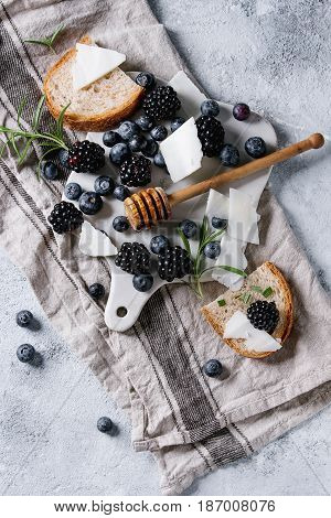 Berries blackberry and blueberry, honey on dipper, rosemary, sliced goat cheese with bread served on ceramic board with textile linen over gray texture background. Summer sandwich. Top view with space