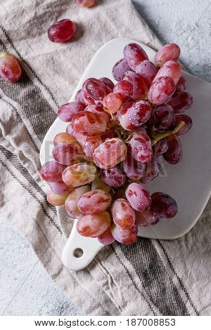 Bunch of red pink ripe wet grapes on white ceramic chopping board with linen kitchen towel over gray blue texture background. Top view with space