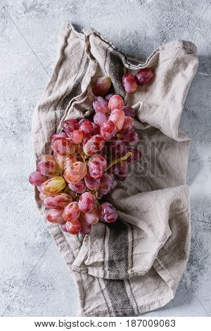 Bunch of red pink ripe wet grapes on linen kitchen towel over gray blue texture background. Top view with space