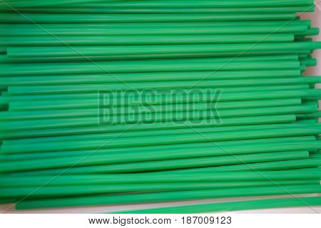 Green plastic drinking straw background, top view
