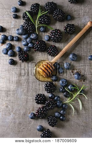 Berries blackberry and blueberry, honey on dipper, rosemary served over gray metal texture background. Summer appetizer. Top view with space