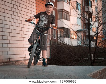 Young boy bmx rider on a ramp with urban background at sunset