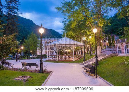 Night scene in central park of Herculane resort, illuminated at night. Romania - Europe