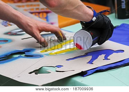 Volgograd Russia - May 25 2013: Graffiti artist's hands drawing figure on fabric using a stencil