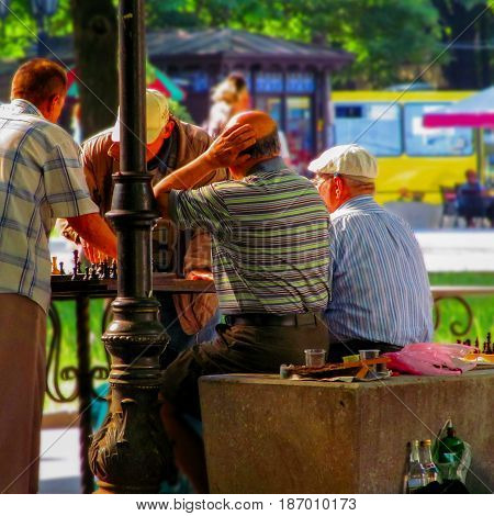 Old men playing chess in the park. Summer bright beautiful photo with a recreation people