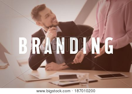 Brand marketing concept. Word BRANDING and business people on background