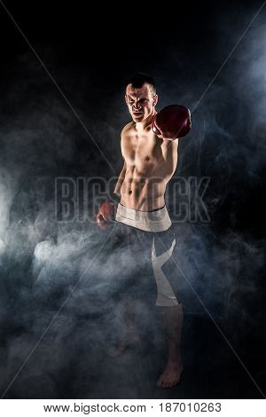 Happy Mixed Martial Arts Fighter With His Arm Raised Forward and Looking at Camera Challenging.