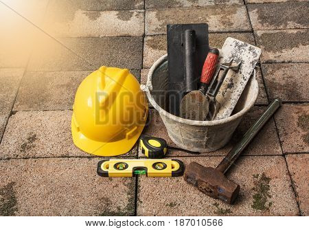 Construction tools or safety equipment with yellow helmet on brick ground
