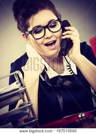 Happy business woman smiling sitting working at desk full off documents in binders calling someone.