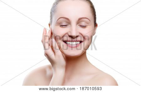 Portrait of a smiling girl with nude make-up with hands on chin isolated on white background. Girl with clean healthy skin on white. Copy space. Beauty model isolated on white. Nude makeup