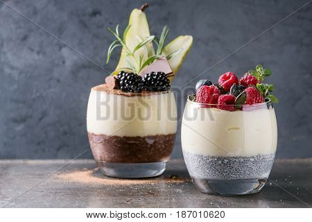 Various dessert breakfast layered chia seeds, chocolate pudding, rice porridge in glass decorated by fresh blackberries, sliced pear, cocoa powder. Stand over gray texture background.