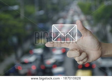 Mail icon on finger over blur of rush hour with cars and road Contact us concept
