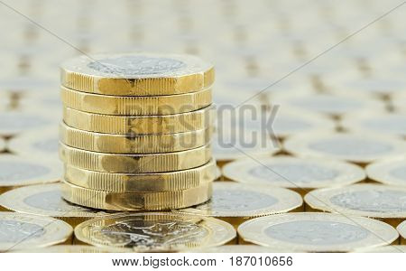 British money new one pound coins in a neat stack on a background of more money. Silver and gold coins introduced in March 2017.
