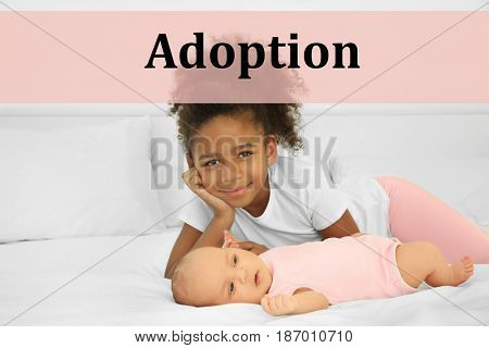 Adoption concept. Cute baby and elder sister lying on bed