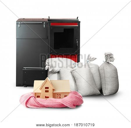 Toy house with bags and solid fuel boiler on white background. Energy savings concept