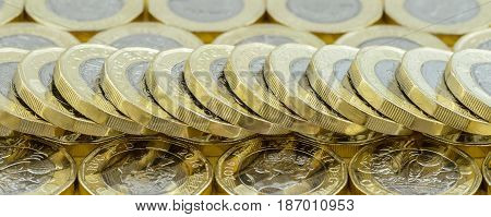 British money pound coins spread out in a fallen stack. New silver and gold coins introduced in March 2017. Banner.