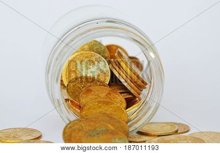 old gold coin apour from glass bottle on white background