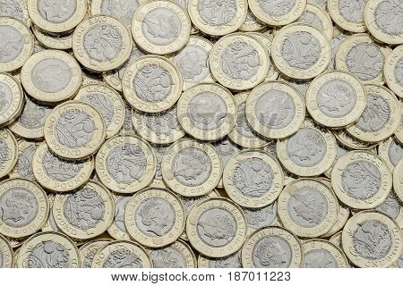Overhead view of British pound coins. Many in an untidy pile. New UK bimetallic currency introduced in March 2017 viewed from above.
