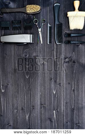 Hairdresser tools on wooden background. Top view on wooden table with scissors comb hairbrushes and hairclips free space. Barbershop