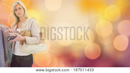 Digital composite of Portrait of woman holding wallet while shopping over bokeh