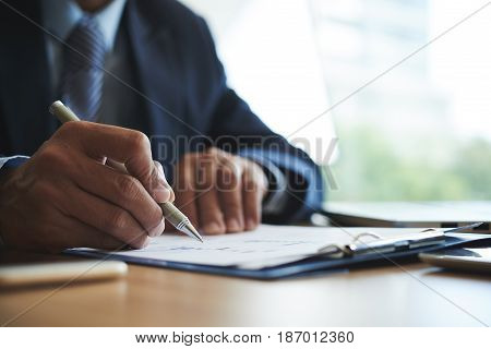 Close-up image of financial manager examining business chart at his table