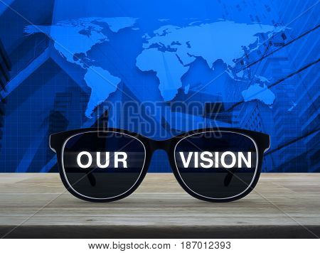 Black glasses with our vision text on wooden table over world map and city tower Business concept Elements of this image furnished by NASA
