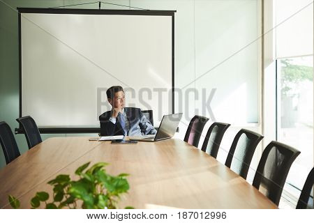 Vietnamese bsuinessman sitting in meeting room and pondering over ideas for business