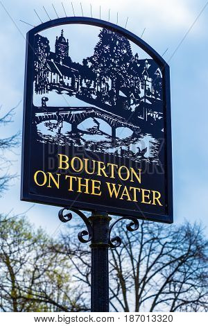 Bourton On The Water England - 7 April 2017 - Bourton On The Water city sign stands against cloudy blue sky on a cloudy spring day at Bourton On The Water England on April 7 2017.