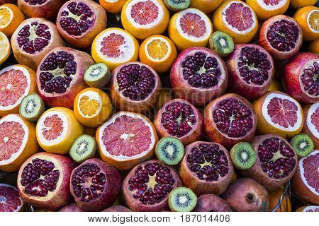 Background of fresh fruits of pomegranate oranges kiwi, pineapple
