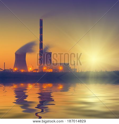 Vintage picture. Coal power plant with rising sun reflected in water.