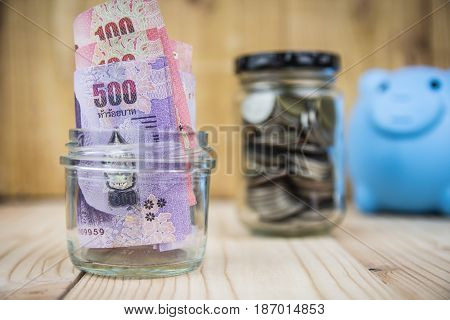 Glass with paper money and coins on wood table.