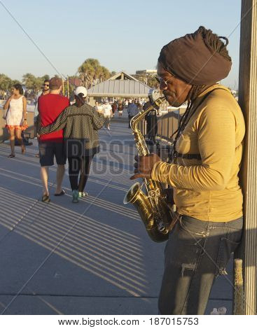 Clearwater Beach; Florida; USA - January 24, 2017: A busker plays the saxophone as people stroll by on Pier 60