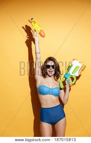 Picture of happy young woman in swimwear isolated over yellow background holding toy water gun. Looking at camera.