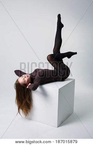 Slim sexy female long legs in black pantyhose in studio on white background