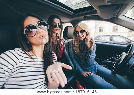 Group Of Girls Having Fun In The Car And Taking Selfies With Camera On Road Trip