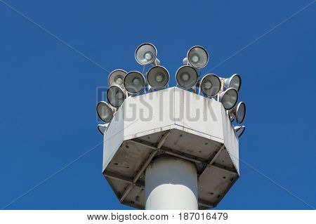 Many speakers on a high tower against a clear sky background.
