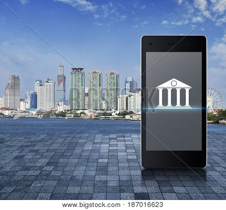 Bank icon on modern smart phone screen on on stone tile floor over modern city tower river and blue sky Mobile banking concept