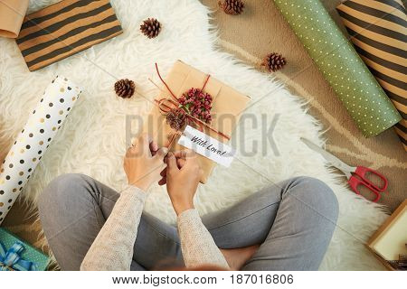 Woman decorating giftbox for a person she loves, view from above
