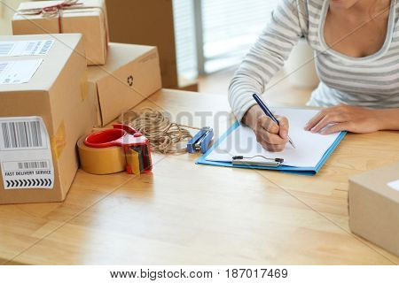 Cropped image of woman making a list of parcels she is going to send