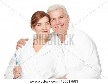 Senior woman with toothbrush and her husband on white background