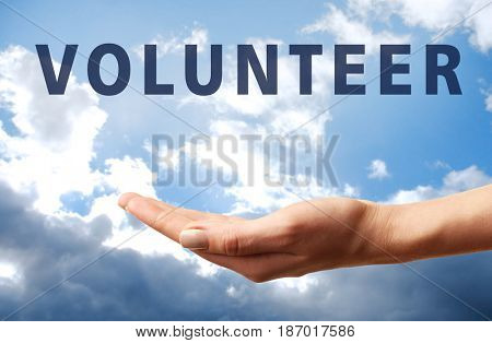 Volunteer concept. Gesture of support with text on sky background