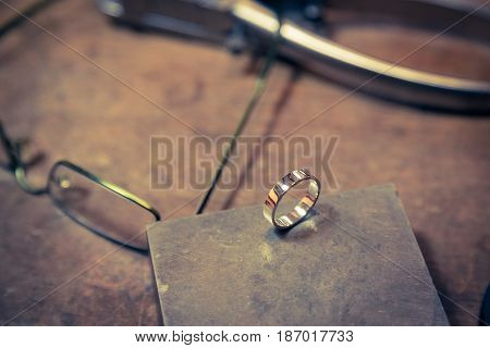 Process of wedding ring crafting. Working desk for craft jewelry making. Final wedding ring product on the table.