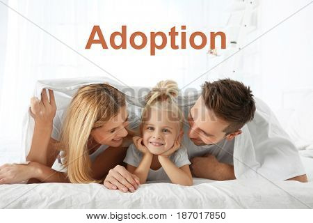Adoption concept. Happy family in bed at home