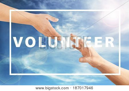 Volunteer concept. Hands reaching to each other and text on sky background