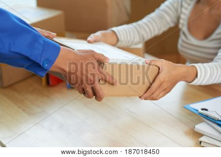 Hands of woman receiving parcel from post worker